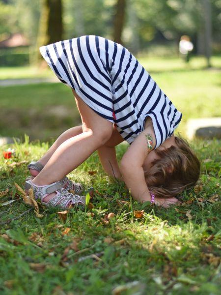 Foto eines Kindes, das einen Salto im Park tut
