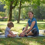 Foto von Beata und von Tochter im Park, nachdem Übungen getan worden sind, die auf einer Decke sitzen