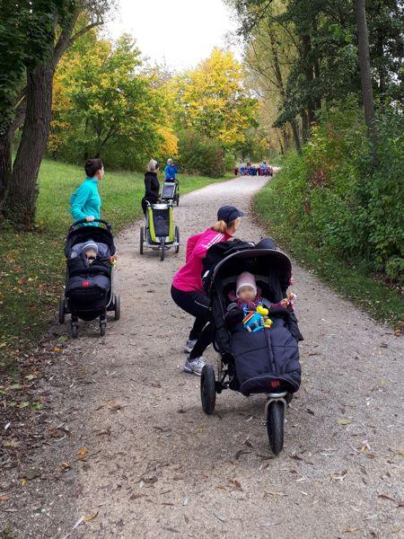 Foto von Müttern in einem Park im Herbst mit ihren Babys in den Kinderwagen, die Training tun